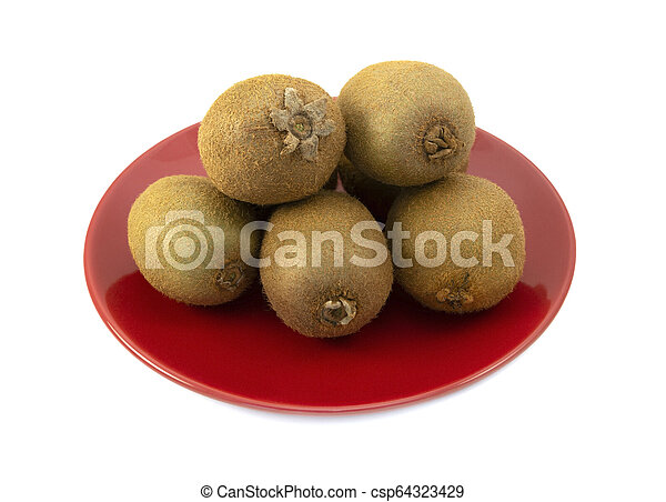 Whole kiwifruits with hairy skins piled on a red plate - csp64323429
