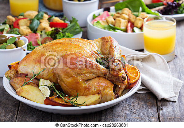 Whole roasted chicken on dinner table - csp28263881