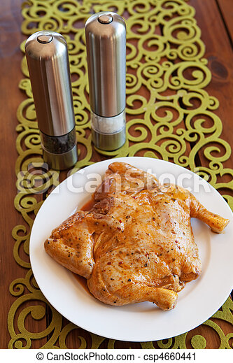Whole uncooked marinated chicken on plate - csp4660441