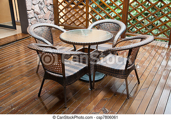 wicker chairs and table on hardwood front deck  - csp7806061