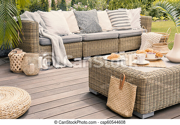 Wicker patio set with beige cushions standing on a wooden board deck. Breakfast on a table on a backyard porch. - csp60544608