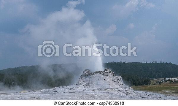 wide shot of castle geyser in yellowstone - csp74368918