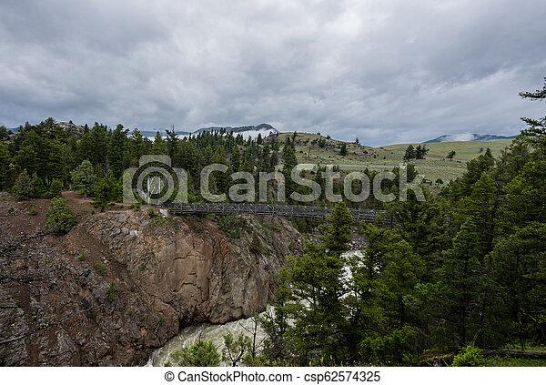 Wide View of Suspension Bridge Over Hellroaring Creek - csp62574325