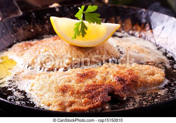 wiener schnitzel frying in a pan  - csp15150810