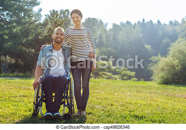 Wife and her husband with disabilities posing in meadow - csp49826346