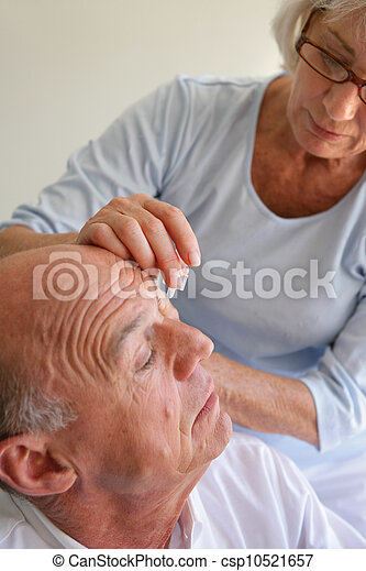 Wife helping husband with eye drops - csp10521657