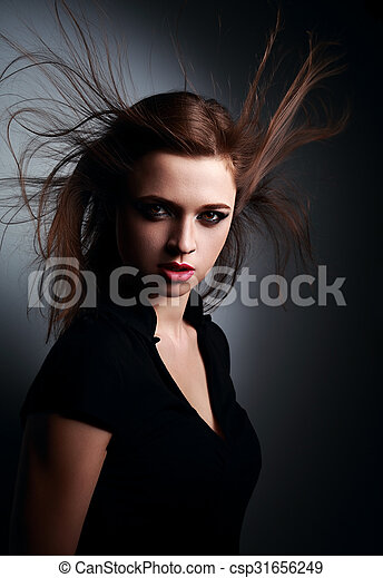 Wild expressive young woman with wind hairstyle and vamp look on dark - csp31656249