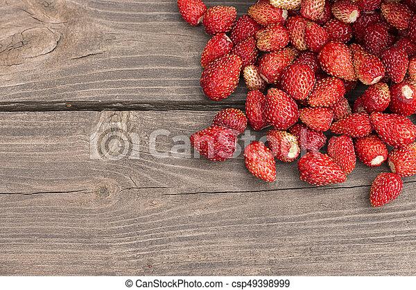 Wild strawberries on rustic wooden background - csp49398999