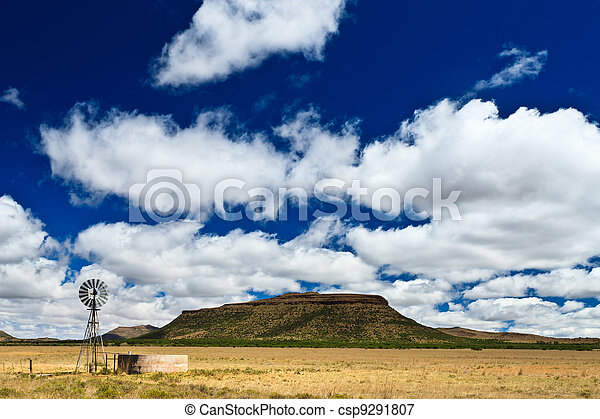 Windmill in a desolate landscape with beautiful cloudscape - csp9291807