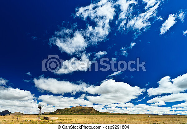 Windmill in a desolate landscape with beautiful cloudscape - csp9291804