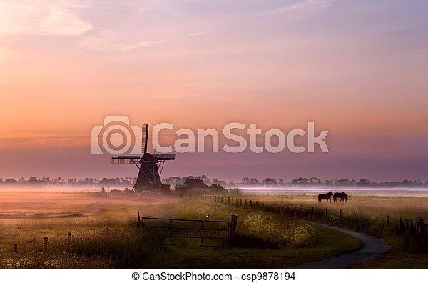 windmill on pasture at sunrise - csp9878194