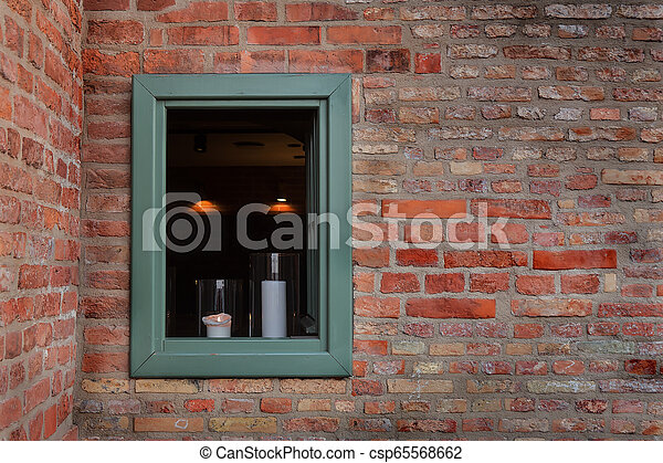 window in a brick wall with candles - csp65568662