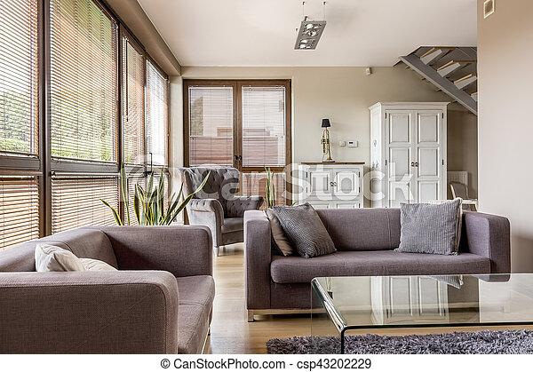 Gemütliches wohnzimmer mit großen fenstern mit jalousien ...