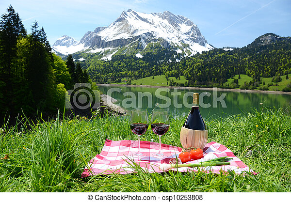 Wine and vegetables served at a picnic on Alpine meadow. Switzerland - csp10253808