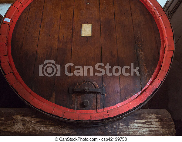 Wine barrel stacked in the old cellar of the winery close up. - csp42139758