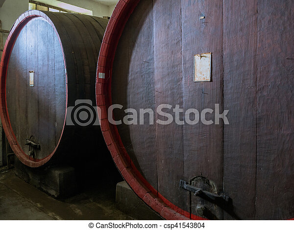Wine barrels stacked in the old cellar of the winery close up. - csp41543804