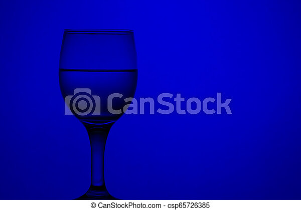 wine glass with water. blue monochrome background - csp65726385