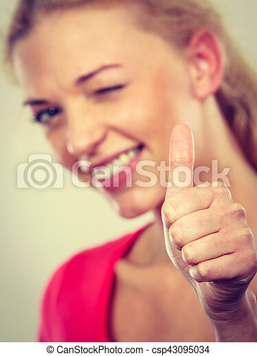 Winking blonde woman showing thumb up - csp43095034