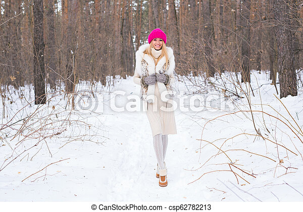 Winter and people concept - Happy blonde young woman in a pink hat and gloves and sweater in the winter forest is smiling and looking straight - csp62782213