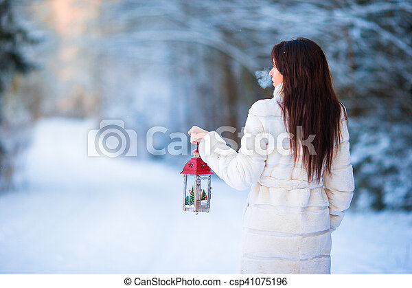 Winter beauty. Woman holding Christmas lantern outdoors on beautiful winter snow day - csp41075196