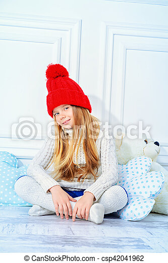 176bc04cb Cute little 7 year old girl wearing knitted winter clothes posing with her  teddy bear. children's fashion.