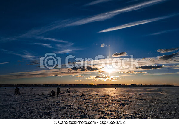 Winter fishing. Silhouette of fishermen catching fish on the icy surface of the river in background the beautiful sunrise - csp76598752