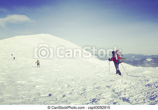 Winter hiking in the mountains on snowshoes with a backpack and tent. - csp43092915