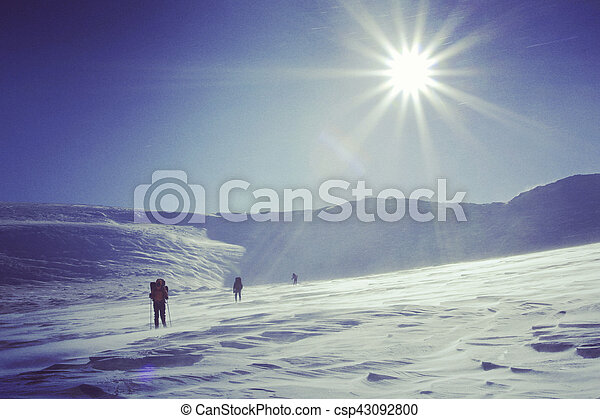 Winter hiking in the mountains on snowshoes with a backpack and tent. - csp43092800