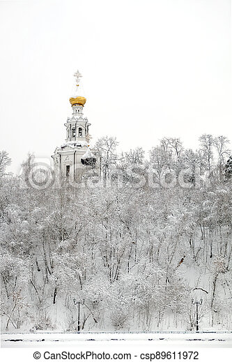 Winter landscape with Russian church on the hill and frozen forest under it in the overcast day - csp89611972