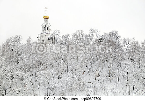 Winter landscape with Russian church on the hill and frozen forest under it in the overcast day horizontal view - csp89607700