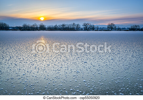 winter sunset over frozen lake in Colorado - csp55050920