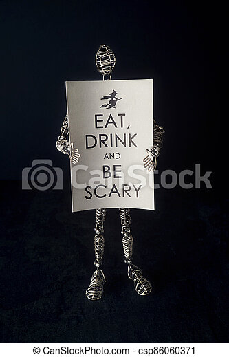 Wire mannequin holding festive halloween card - csp86060371