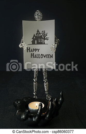 Wire mannequin holding  halloween card with candle - csp86060377
