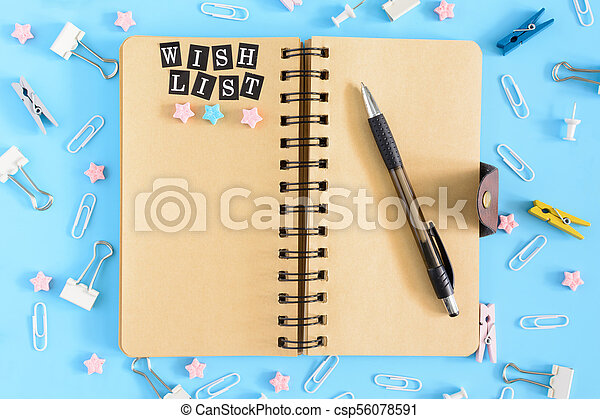 Wish list. Notepad with brown sheets and an inscription . Confusion of office supplies. Clips, clothespins and small sprockets scattered on a blue background. - csp56078591