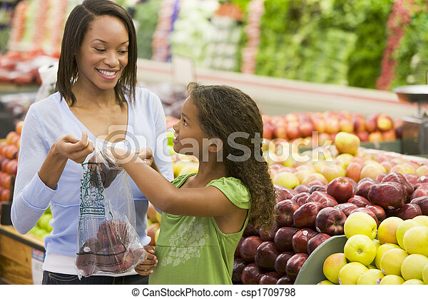 Woman and daughter shopping for apples at a grocery store - csp1709798