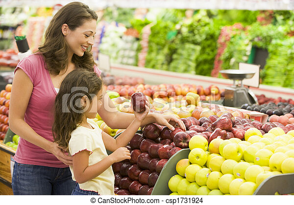 Woman and daughter shopping for apples at a grocery store - csp1731924