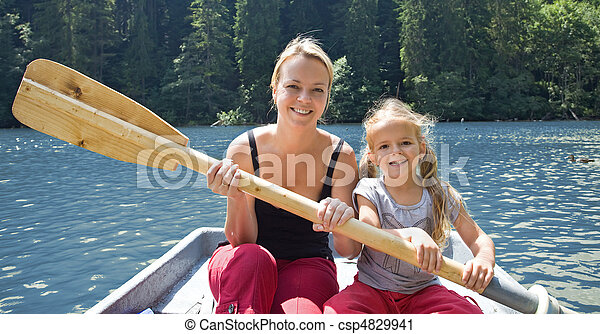 Woman and little girl on the lake in a little boat - csp4829941