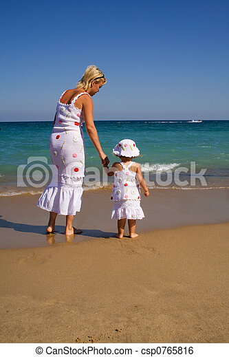 Woman and little girl walking on the beach - csp0765816