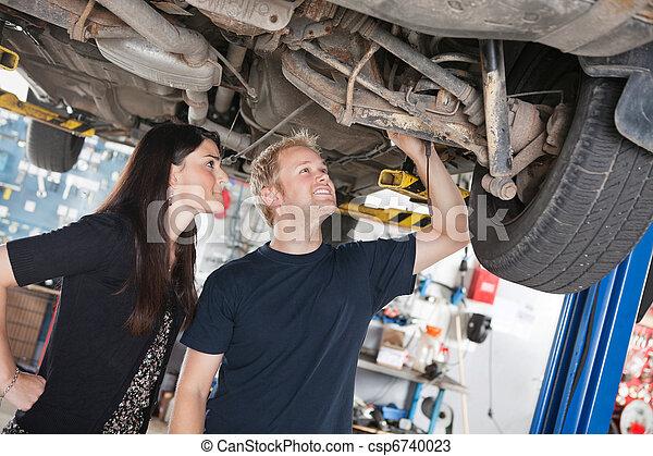 Woman and mechanic looking at car repairs - csp6740023