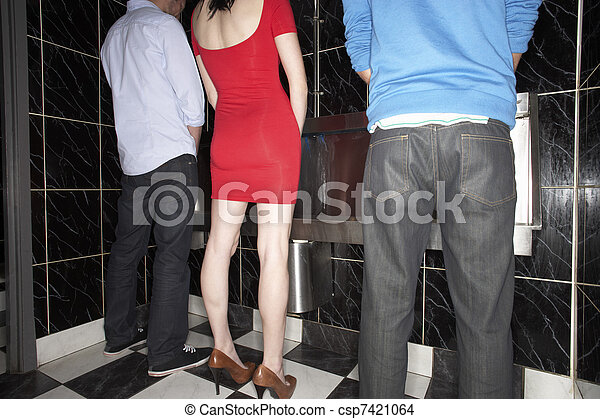 Woman and two men standing at mens urinal - csp7421064