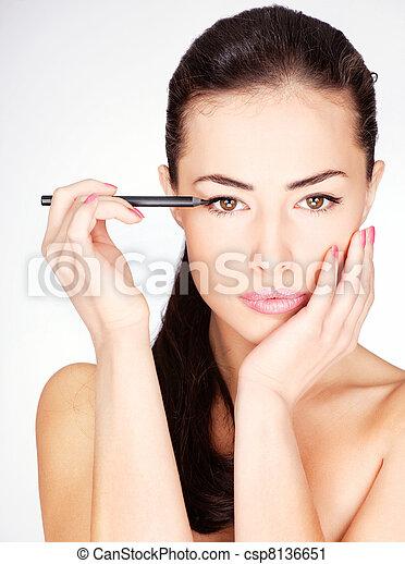 woman applying cosmetic pencil on eye - csp8136651