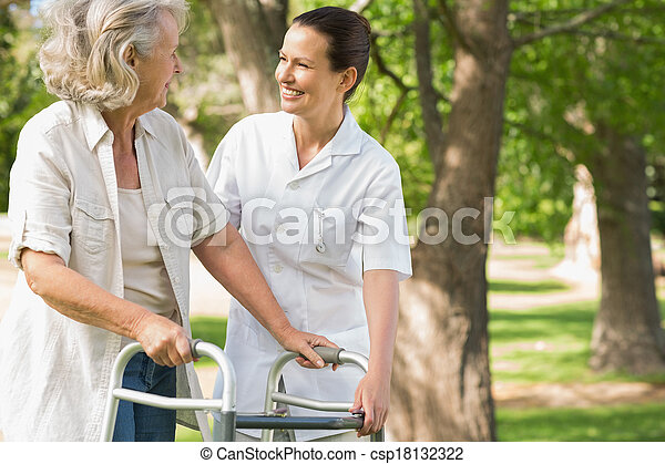 Woman assisting mature female with walker at park - csp18132322