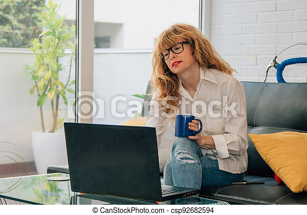 woman at home with computer and cup of coffee sitting on the sofa - csp92682594