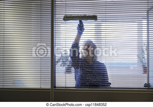 Woman at work, professional female cleaner cleaning and wiping window in office with detergent - csp11848352