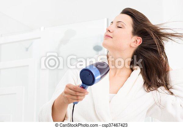 Woman blow-drying hair - csp37467423