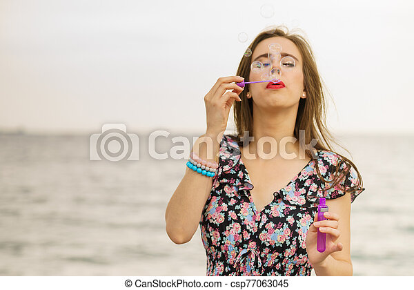Woman blowing bubbles outdoor - csp77063045