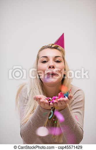 woman blowing confetti in the air - csp45571429