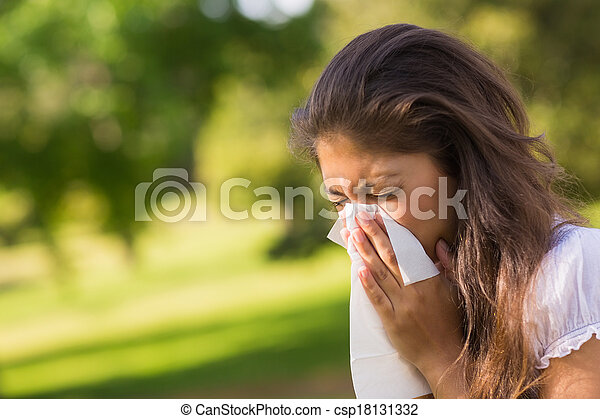 Woman blowing nose with tissue paper at park - csp18131332