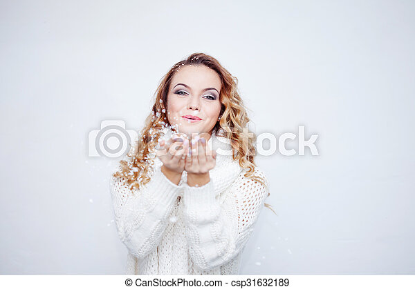 Woman Blowing Snow, girl in  warm knitted scarf, portrait on  white background, place for your text - csp31632189
