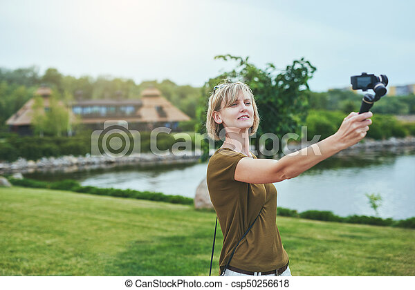 Woman capturing herself with personal camera - csp50256618